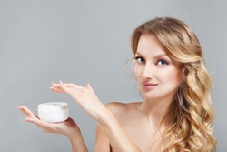 skin care. Beautiful blondhair girl keeping jar with cosmetic cream in hands