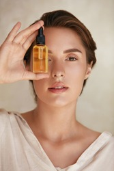 Skin Care. Beauty Portrait Of Woman Holding Bottle With Dropper Near Face. Model Using Natural Cosmetic Product For Hydrated, Glowing And Healthy Facial Derma. Essential Oil For Anti-Aging Therapy.