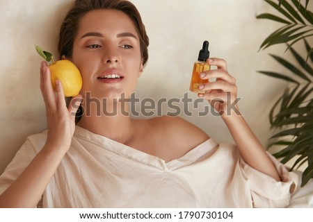Skin Care. Beauty Portrait Of Woman Holding Lemon And Bottle Near Face. Natural Cosmetic Product For Hydrated Healthy Facial Derma. Essential Oil And Vitamin C For Anti-Aging Therapy. Zdjęcia stock ©