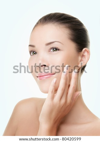 Skin care beauty woman. Beauty woman smiling applying cream. Beauty portrait of beautiful Asian / Caucasian female model isolated on light blue background looking at copy space.