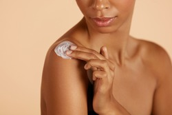 Skin care. Closeup woman's body with cosmetic cream on skin. Beautiful black girl with moisturizing lotion on hydrated body skin at studio