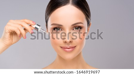 Skin care concept. Beauty portrait of smiling young woman girl holding pipette with cosmetic oil  or  serum near clean face. Cosmetology and Spa