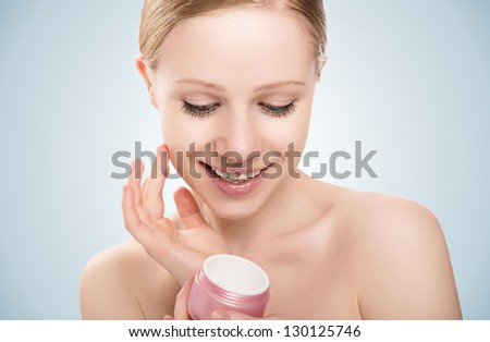 skin care. face of a happy beauty healthy girl with eyes closed with jar of