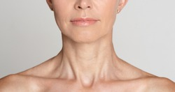 Skin care. Half face portrait of mature woman with wrinkled neck, grey background, crop