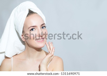 Skin care of the face girl gets cream in the face. On white background. #1311690971