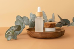 Skin care packaging and bottle with dropper from frosted glass,staying in wooden plate.Fresh eucalyptus branch behind.Pastel isomeric background.Cosmetics banner with copy space.Zero waste packaging.