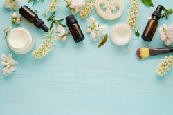 Skin care products flat lay composition with spring flowers on blue background, space for text.
