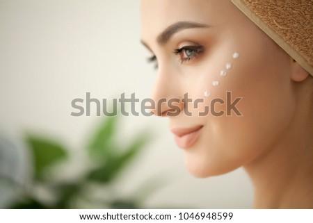 Skin care. Studio shot of beautiful young woman applying moisturizer cream onto her face #1046948599