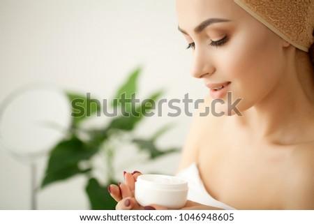 Skin care. Studio shot of beautiful young woman applying moisturizer cream onto her face #1046948605
