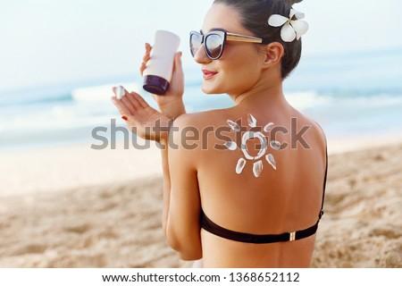 Skin care. Sun protection. Woman apply sun cream. Girl Holding Moisturizing Sunblock. Woman With Suntan Lotion On Beach In Form Of The Sun. Portrait Of Female With  Drawn Sun On A Shoulder. Suncream.