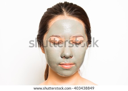 Skin care. Woman applying with brush clay mud mask on face isolated. Girl taking care of dry complexion. Beauty treatment. #403438849