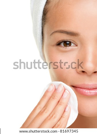 skin care woman removing face makeup with cotton swab pad - skin care concept. Facial closeup of beautiful mixed race Chinese Asian Caucasian model with perfect skin. Girl isolated on white background