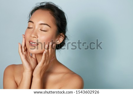 Photo of  Skin care. Woman with beauty face and healthy facial skin portrait. Beautiful asian girl model with natural makeup touching glowing hydrated skin on blue background closeup. High quality image