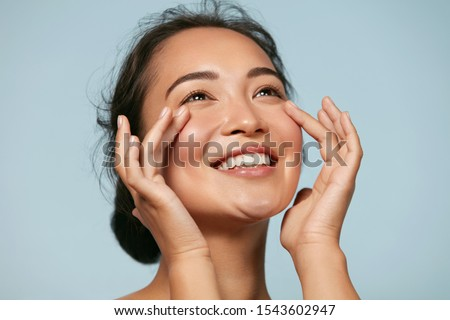 Photo of  Skin care. Woman with beauty face touching healthy facial skin portrait. Beautiful smiling asian girl model with natural makeup touching glowing hydrated skin on blue background closeup