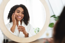Skin Hydration. Positive black woman applying moisturizing serum on face, looking to mirror and smiling