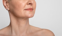 Skin Lifting. Cropped image of mature woman with smooth skin over light background, closeup