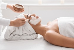 Skin Lifting Treatment. Young asian woman getting facial nourishing mask by professional beautician at spa salon, calm lady enjoying wellness day and beauty procedures, side view with copy space