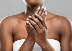 Skin nutrition concept. Unrecognizable african american woman applying moisturizing cream to her hands over gray studio background, crop