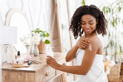 Skin Nutrition. Smiling Attractive Black Woman In Towel Applying Body Lotion, Pampering Herself After Bath, Sitting Wrapped In Towel At Dressing Table