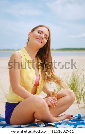 Skin protection in summer. Woman on beach using sun oil. Young beauty girl taking sunbath on sunny day. Holidays time. #1161882961