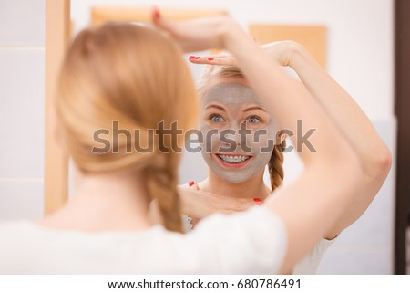 Skincare. Blonde woman in bathroom with gray clay mud mask on her face. Young lady taking care of skin. Spa beauty wellness. #680786491