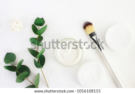 Skincare cosmetics with aroma eucalyptus plant extract. Jar of organic beauty product and application brush with fresh green leaves herbal bough, top view white background. Home spa and body care. #1056108155