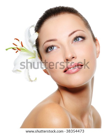 Skincare of young beautiful woman face with  fresh flower over white background