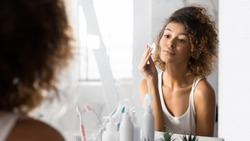 Skincare Routine. African American Girl Removing Makeup Using Cotton Pad Looking In Mirror Standing In Bathroom. Panorama