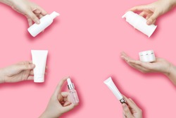 Skincare routine step for healthy skin - Woman hands holding foam, essential oil, serum, lotion, cream and lip balm packaging on pink background. Beauty and cosmetic concept. Copy space.