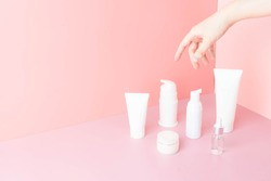 Skincare routine- Women hand choosing skin care products for healthy skin on pink background. Packaging of facial foam, cleansing, essence, serum, cream/lotion. Beauty and cosmetic concept. Minimal.
