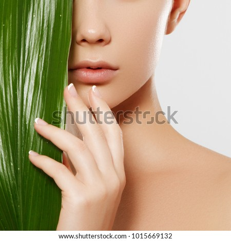 Skincare, Wellness, Spa. Clean soft Skin, healthy Fresh look. The concept of a healthy skin. Portrait of a beautiful girl against a background of tropical leaves. Spa concept. Natural beauty #1015669132