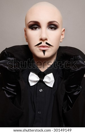 Skinhead girl in black clothes and false mustache on her face