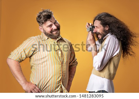 Skinny artist taking a photo-portrait of a cheerful, plump friend