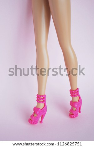 Skinny doll legs with pink high heels shoes.