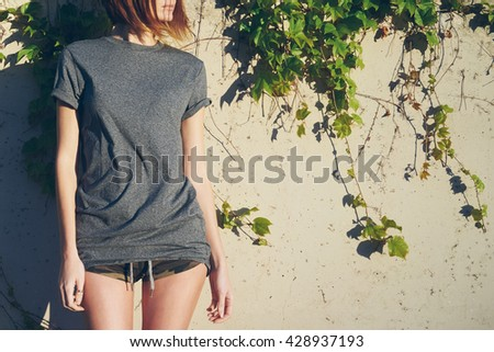 Skinny girl in a gray blank t-shirt is looking aside. A young model look woman is standing beside the wall overgrown with ivy.