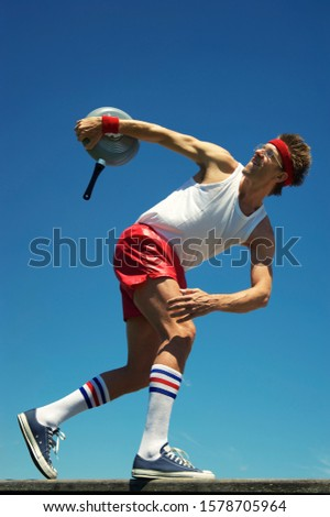 Skinny nerd athlete in hipster athletic sportswear practicing for a track and field discus throw athletics event with a frying pan