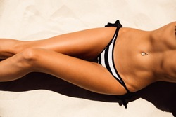 Skinny young beautiful woman in a striped black and white bikini sunbathing on the soft sandy sea shore. Outdoor lifestyle picture on a hot sunny summer day.