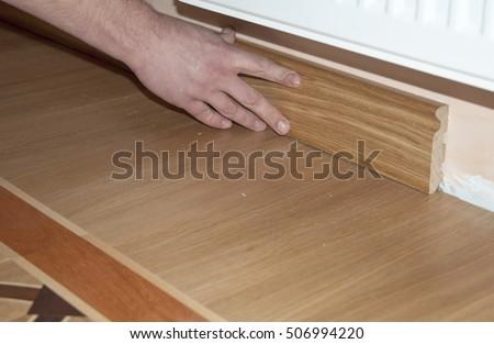 Skirting Board & Architrave. Repairman's hands Installing Skirting Board Oak Wooden Floor with Glue. Flooring and Repair.