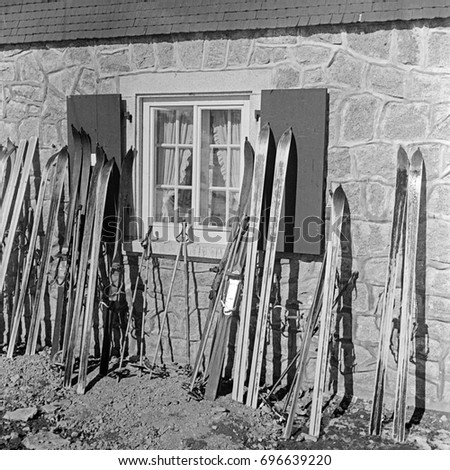 Skis and ski poles leaning outdoors on house wall