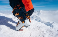 Skis boots while preparing for skiing. The skier wears footwear for skiing and fixes the fastener