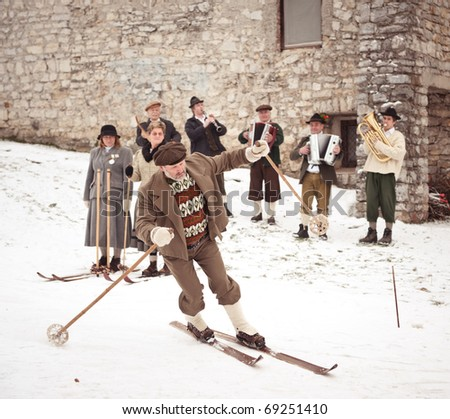 SKOFJA LOKA, SLOVENIA - JANUARY 3: Rovtarji skiers in traditional retro style costumes, with old wooden ski gear skiing at Old-style skiing performance on January 3, 2011 in Skofja Loka, Slovenia