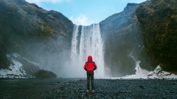 Skogafoss waterfall in Iceland. Guy in red jacket looks at Skogafoss waterfall.