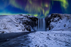 Skogafoss waterfall in the winter at night under the northern lights. Iceland