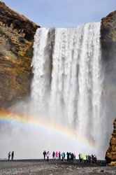 Skogafoss waterfall with rainbow and silhouette of some tourist, Iceland