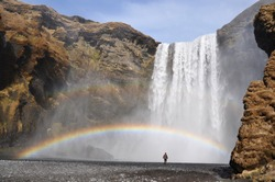 Skogafoss waterfall with rainbow and silhouette of standing men as a scale, Iceland