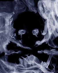 Skull and bones shape formed from cigarette smoke, over black, abstract photo manipulation, blue toned studio shot.