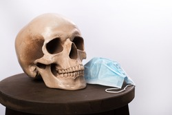 skull and medical mask lie on a wooden stand on a white background. place for text. coronavirus protection concept