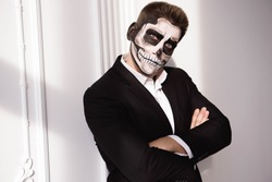 Skull make up portrait of young man. Halloween face art.