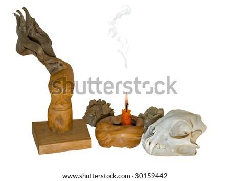Skull of animal, burning candle and wood idol.