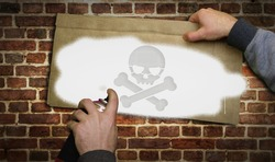 Skull piracy symbol spray painted on the brick wall. Graffiti art concept of piracy, danger and warning. Urban abstract artwork. Airbrush paint with sign template in hand.